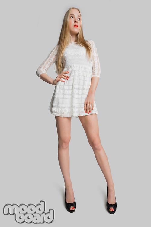 Confident stylish teenage girl posing over gray background