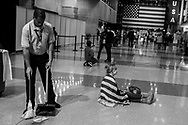 A man cleans the floor as the last supporters watch the election returns during Democratic presidential nominee Hillary Clinton's election night rally in the Jacob Javits Center glass enclosed lobby in New York, Wednesday, Nov. 9, 2016.