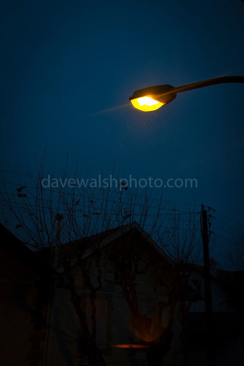 Streetlight in the rain, early morning in  Biarritz, with a wild Atlantic Ocean.