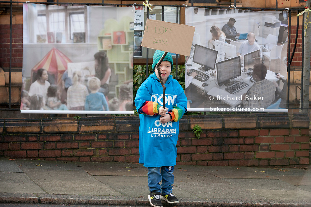 A young boy protests outside Carnegie Library on Herne Hill in south London which re-opens for the first time in almost 2 years, on 15th February 2018, in London, England. Closed by Lambeth council and occupied by protesters for 10 days in 2016, the library bequeathed by US philanthropist Andrew Carnegie has been locked ever since because, say Lambeth austerity cuts are necessary. A gym that locals say they don't want or need has been installed in the listed basement and actual library space a fraction as before and it's believed no qualified librarians will be present to administer it. Protesters also believe this community building will ultimately sold off by Lambeth council for luxury homes.