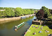 Narrow boats on River Avon and people in Parade Gardens, Bath