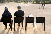 Elderly couple sitting outside in a garden