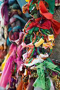 THIMMAMMA MARRIMANU, INDIA - 28th October 2019 - Prayer offerings tied to Thimmamma Marrimanu banyan tree - the world's largest single tree canopy. Andhra Pradesh, India. <br /><br />Many believe that the tree has mystical powers and is able to bless childless couples with the gift of fertility. There is a very strong belief that if a person or couple ties a saffron ribbon, bangles or a small pouch containing natural offerings like leaves and spices to the tree, the goddess will bless them with fertility within one year of placing the offering.