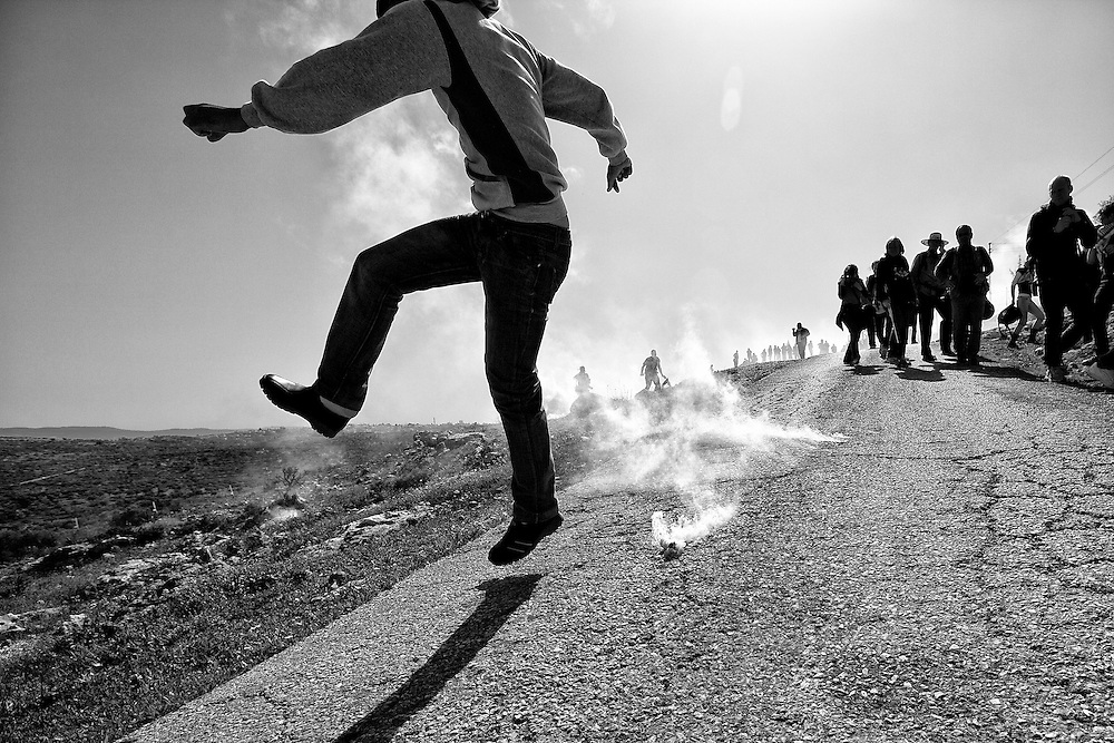 A Palestinian boy kicks a tear gas canister down the hill and away from others who were within range of Israeli fire. Bil'in. Mar. 4, 2011. West Bank, Palestine.