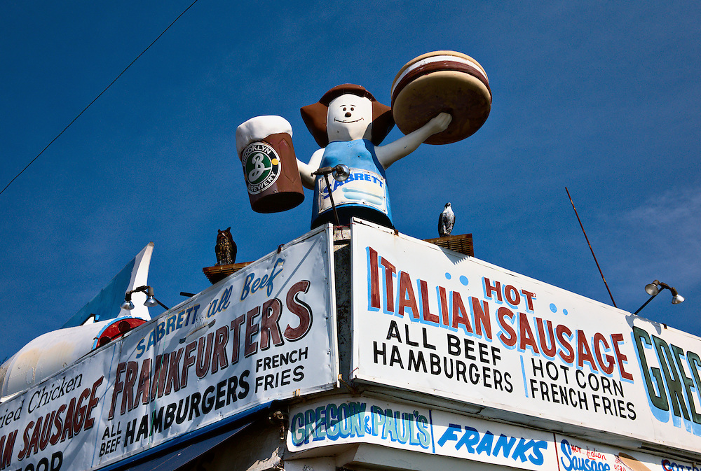 Sign advertising hot dogs and Italian sausage, with cartoon-like figure holding giant burger and beer mug, Coney Island, New York