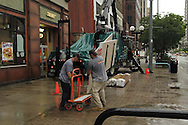Workers try and get building materials inside quickly while it's raining in downtown Dayton, Wednesday, June 4, 2008.