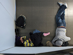 Travelers stranded by the ash cloud from a volcanic eruption in Iceland, sleep at Schiphol Airport in Amsterdam, the Netherlands, on Tuesday, April 20, 2010. (Photo © Jock Fistick)
