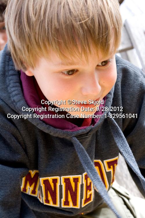 Portrait of happy boy age 9 wearing a Minnesota sweatshirt St Paul Minnesota MN USA