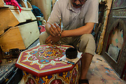 Painter finishing a beautiful wooden table in Marrakech souks