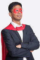 Young Asian businessman in superhero's costume with arms crossed against white background