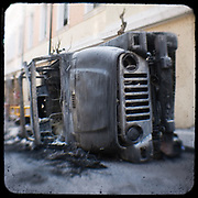 A burned, overturned Jeep in Sina street Athens. <br /> <br /> The killing of the 15 year old boy Alexandros Grigoropoulos by a policeman resulted in widespread riots that altered the city landscape. <br /> <br /> When I walked in the streets of my town the day after the riots I instantly forgot the image I had about Athens, that of a bustling, peaceful, energetic metropolis and in my mind came the old photographs from WWII, the civil war and the students uprising against the dictatorship. <br /> <br /> Thus I decided not to turn my digital camera straight to the destroyed buildings but to photograph through an old camera that worked as a filter, a barrier between me and the city.