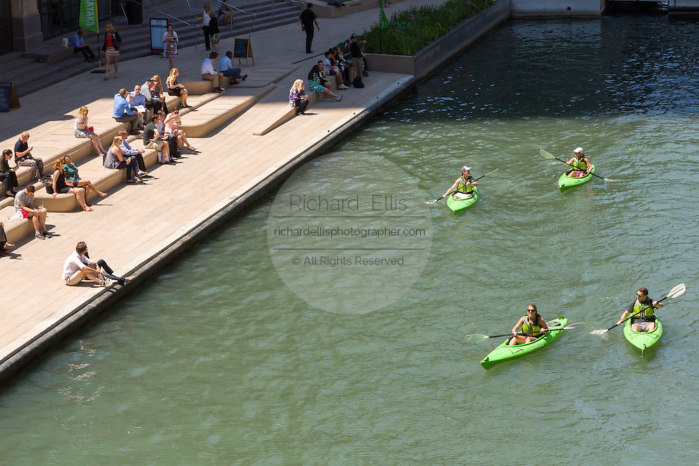 Kayakers on the Chicago River stop at the Riverwalk on a summers day in Chicago, Illinois, USA