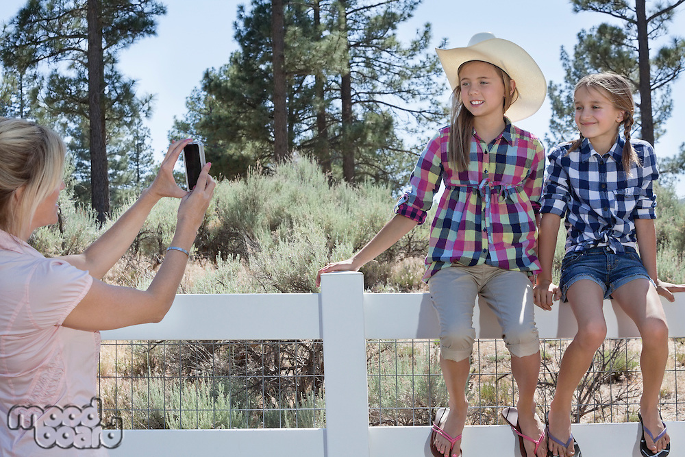 Mother photographing daughters through cell phone as they sit on fence at park