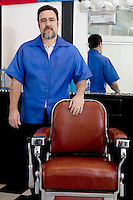 Portrait of a mature barber standing near seat