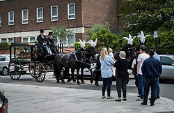 © Licensed to London News Pictures. 29/06/2017. London, UK. Mourners look on as the coffin of Grenfell Tower fire victim Tony Disson is carried in a horse drawn hearse to Our Lady of the Holy Souls church for a funeral service in Kensal, West London. Mr Disson is one of only a handful of the 80 victims to have been identified and named so far. Photo credit: Peter Macdiarmid/LNP