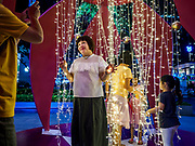 "12 DECEMBER 2018 - SINGAPORE:  A woman poses for pictures in a display that resembles Christmas ornaments on Orchard Road. Orchard Road is the main shopping district of Singapore and for years hosts a large light display around Christmas. The main sponsor of this year's display is the Disney Company and the displays are decorated with characters from the Disney entertainment universe. This has upset some religious leaders in Singapore and the National Council of Churches of Singapore (NCCS) sent a letter to the Singapore Tourism Board (STB) expressing its concern about the ""increasing secularisation and commercialization of Christmas"" in Singapore. The STB reached out to the NCCS, but the Orchard Road lights will remain on through the holidays.  PHOTO BY JACK KURTZ"