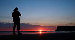 © Licensed to London News Pictures. <br /> 17/04/2015. <br /> <br /> Saltburn, United Kingdom<br /> <br /> A man out for an early morning walk stops to look at a spectacular sunrise at Saltburn in Cleveland.<br /> <br /> Photo credit : Ian Forsyth/LNP