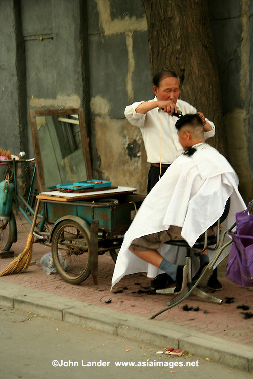 Al Fresco Barber in the Beijing Hutongs -  Beijing traditional hutong life is now being protected in an attempt to preserve this aspect of Chinese cultural history and way of life.Hutong life, as described by Beijingers, usually means local or courtyard life.  Yet the hutong, or alleys, are dear to the hearts of the citizens of this city.  Hutong life refers not only to the alleyways, but mostly to the neighborly way of life that is said to be disappearing.