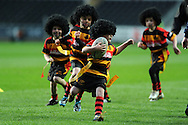 Abercrave RFC junior players, wearing black 'Adam Jones' wigs playing tag rugby during halftime of Ospreys match at the Liberty Stadium in Swansea on Saturday 31st March 2012. pic by Andrew Orchard