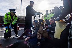 "© Licensed to London News Pictures. 19/11/2016. Heathrow, UK. An activist remonstrates with police while they attempt to cut her and other activists from the road surface.  A group of activists stage attach themselves to a road surrounding  Heathrow Airport, during a demonstration against the expansion of Heathrow Airport and the building of a third runway. Some activists  threatened ""direct action"". Photo credit: Ben Cawthra/LNP"