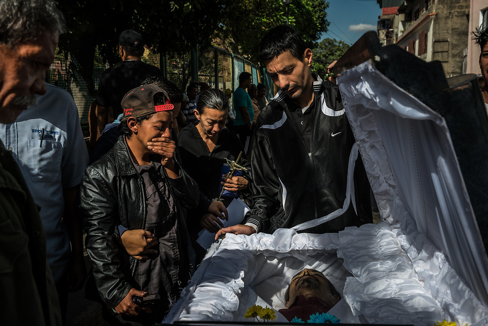 "PETARE, VENEZUELA FEBRUARY 23, 2018:  Friends and family mourn the death of mechanic, Víctor Martínez, 47, who died on February 22, 2018 from tuberculosis.  Before he died, he lost a significant amount of weight, and was coughing uncontrollably – often coughing up phlegm that family members described as, ""as dark as Pepsi cola"". PHOTO: Meridith Kohut for The New York Times"