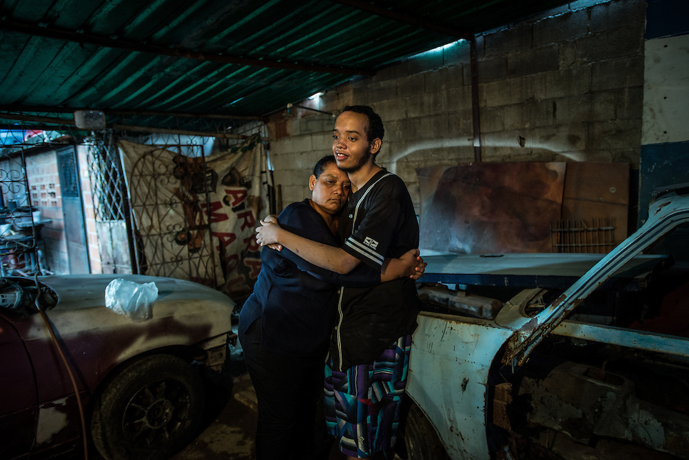 "MARACAY, VENEZUELA - JULY 15, 2016: Evelin RodrÍguez indulges in a rare moment of affection from her schizophrenic son, Gerardo.  He spends most of his days either sleeping, or standing in a corner in silence in his family's living room, refusing to talk or respond to questions, and rarely even making eye contact with members of his family.  His parents remember how he used to be when he was younger…before he became ill - recalling how affectionate and talkative he was. ""He was so kind and loving,"" said his mother, Evelin. On rare occasions Gerardo will smile and offer a hug. Evelin leads a difficult life caring for Gerardo and his brother Accel, who also suffers from schizophrenia. Venezuela is suffering from severe shortages of medicines, including the psychiatric drugs that she needs to keep her sons' conditions stabilized. It is an exhausting task taking care of them and going from pharmacy to pharmacy for hours searching for the medicines that her sons need, that she is rarely able to find. She loves her sons but says she is tired. She cherishes the small moments when she is able to connect to Gerardo like this one when he reached out to hug her.  PHOTO: Meridith Kohut for The New York Times"