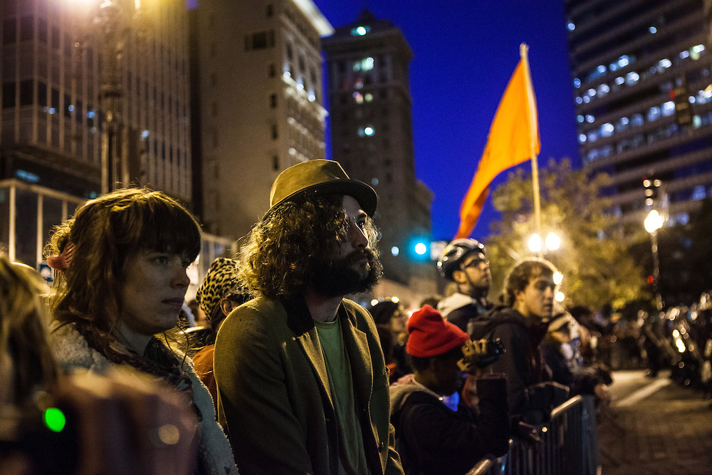 OAKLAND, CA - NOVEMBER 14, 2011: Occupy Oakland protesters look on in utter silence as they watch their encampment being broken down. The crowd was uncharacteristically calm, seemingly understanding that not much could be done at this point.
