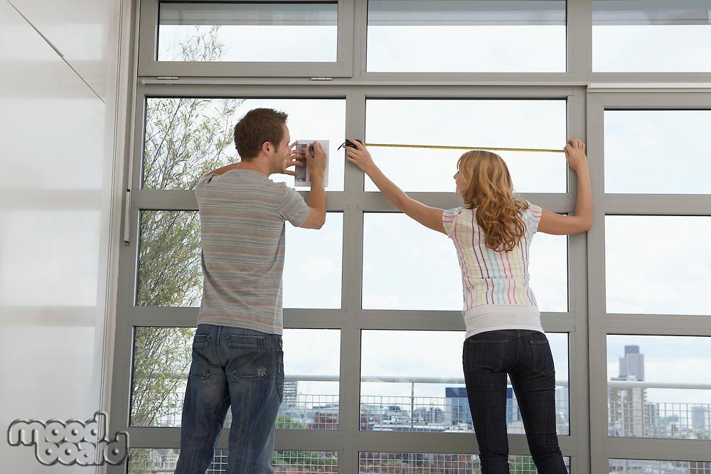 Couple measuring apartment window