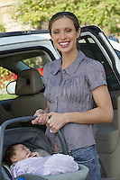 Portrait of woman with baby (1-6 months) in carrier by car