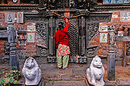 A woman applying vermilion on the statue of Lord Mahavira in Chatu-Brahma Mahavihar temple in Bhaktapur, Nepal.