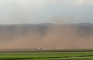 Goshen, New York - A pickup truck drives through a dust storm as strong winds carry soil into the air over farmers' fields in the Black Dirt region of Orange County on May 8, 2010. Winds gusted at up to 40 miles per hour. ©Tom Bushey / The Image Works