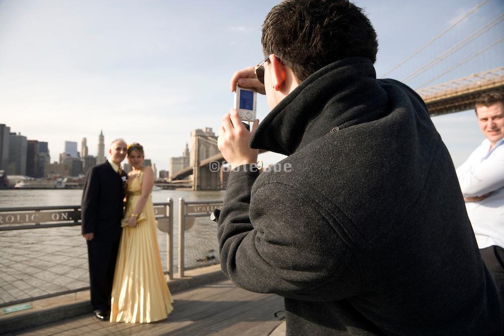 middle aged couple being photographed with Brooklyn Bridge and down town Manhattan in the background