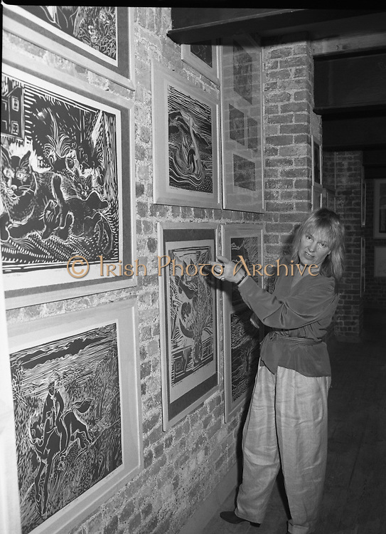 "Pauline Bewick Art Exhibition..1986..03.06.1986..06.03.1986..3rd June 1986..At the Guinness Hop Store,Dublin,artist Pauline Bewick is having an exhibition of her work.The exhibition called ""2 to 50 years""is a display of her work from age 2 to the present.the art work ranges from simple pencil sketches to more complex paintings and lino cuts...Picture shows the artist,Pauline Bewick,with a selection of her lino cuts which she has on display on the walls of The Hop Store."