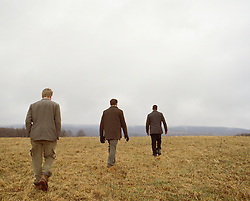 three men walking away from camera out in a field in Upstate New York