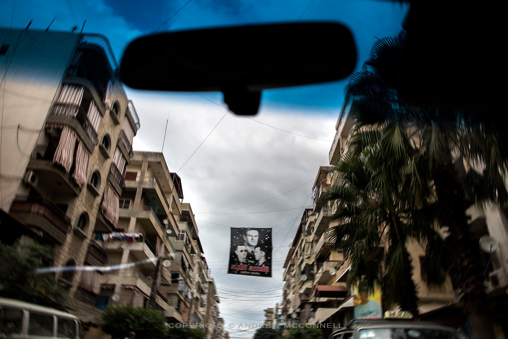 A poster featuring Syrian president Bashar al-Assad, his father, Hafez al-Assad, and brother, Maher al-Assad, hangs above the Alawite muslim neighbourhood of Jabel Moshen, in Tripoli, Lebanon. Jabel Moshen is home to the majority of Lebanon's Alawite community, thought to number approximately 120,000. They have close ties to the Alawite community in Syria and the area has seen sectarian clashes with the adjacent Sunni muslim quarter, Bab al-Tabbaneh, as far back as the civil war.