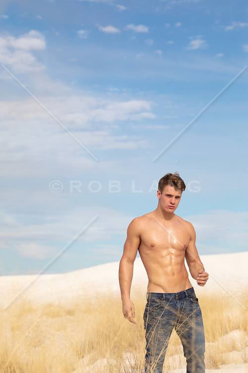 shirtless muscular man in jeans on a sand dune