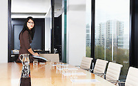 Business woman sitting on table in boardroom
