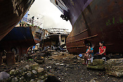 April 18, 2014 - Tacloban, Philippines. Women seek shade under the hulls of several beached ships that were blown inland by typhoon Haiyan. Typhoon Haiyan struck the central Philippines on November 8, 2013, leaving more than 5000 dead and displacing nearly 2 million people homeless.
