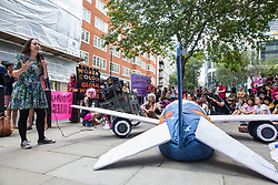 London, UK. 29 July, 2019. Amelia Womack, Deputy Leader of the Green Party, addresses activists from Reclaim the Power, All African Women's Group, Docs Not Cops, Lesbians and Gays Support the Migrants and other groups at a protest outside the Home Office alongside a model of an aircraft used for deportation flights to demand an end to the Government's 'hostile environment' policies.