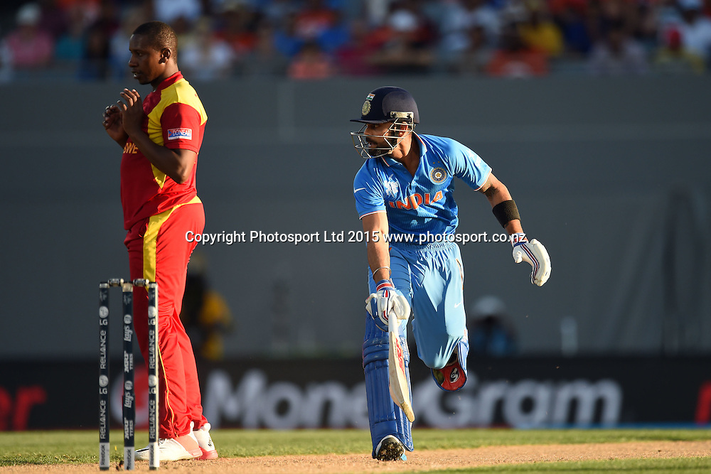Indian batsman Virat Kohli makes his ground comfortably as bowler Tendai Chatara looks on during the ICC Cricket World Cup match between India and Zimbabwe at Eden Park in Auckland, New Zealand. Saturday 14 March 2015. Copyright Photo: Raghavan Venugopal / www.photosport.co.nz