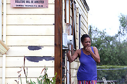 August 26, 2017 - Corpus Christi, TX, USA - Beverly Perryman stands outside her home and watches as her nephew cuts down a tree with a machete in the Hillcrest neighborhood of Corpus Christi, Texas, on Saturday, Aug. 26, 2017, the morning after Hurricane Harvey. She said, ''The house got to shaking, it tore the stuff off our roof.'' She doesn't have insurance. (Credit Image: © Rachel Denny Clow/TNS via ZUMA Wire)