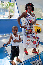 Bahamian mother and son posing for a picture on the Blue Manta boat.