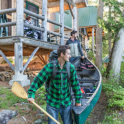 Two men carry a canoe past the cabins at the Appalachian Mountain Club's Gorman Chairback Lodge. Near Greenville, Maine.