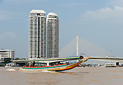 A long tail boat motors on Chao Phraya past by Rama VIII Bridge and modern skyscrapers in Bangkok, Thailand, Asia. Rama VIII Bridge opened on September 20, 2002. A single pylon elegantly suspends the stay cables. The popular bridge is depicted on the Series 15 20-baht banknote, behind a portrait of the bridge's namesake, King Ananda Mahidol, eighth monarch of the Chakri dynasty.