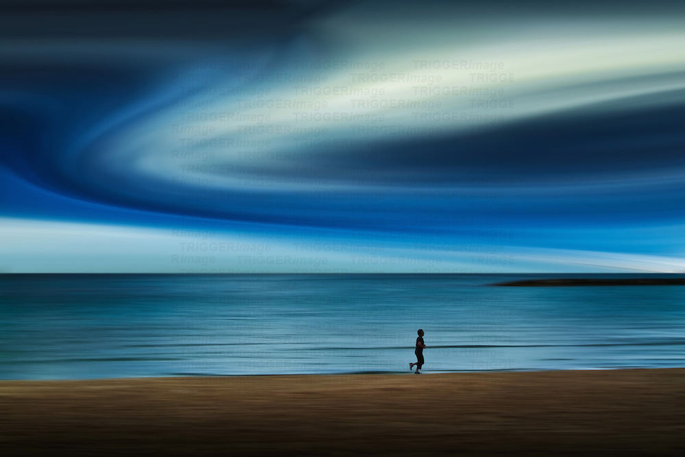 Conceptual beach scene with male runner under blue sky