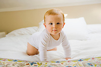 Portrait of a 10 month old baby crawling on a bed.