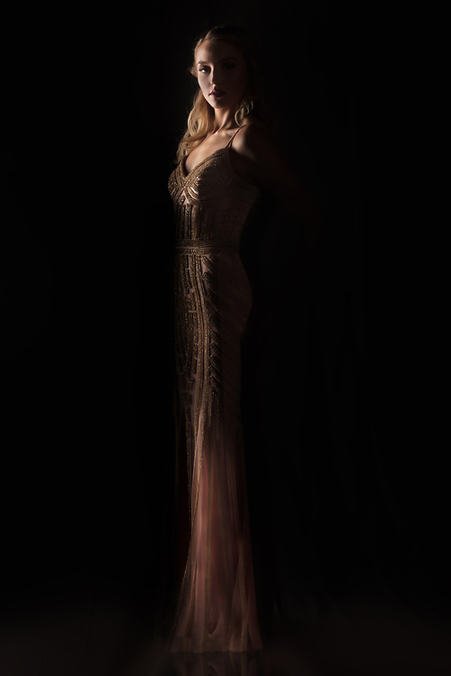 Low key fashion photograph of model Savannah Galloway in evening gown for Houston Fashion Week runway show.