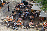 Diners at pavement cafe and cobbled pavement in St Emilion, Bordeaux region of France