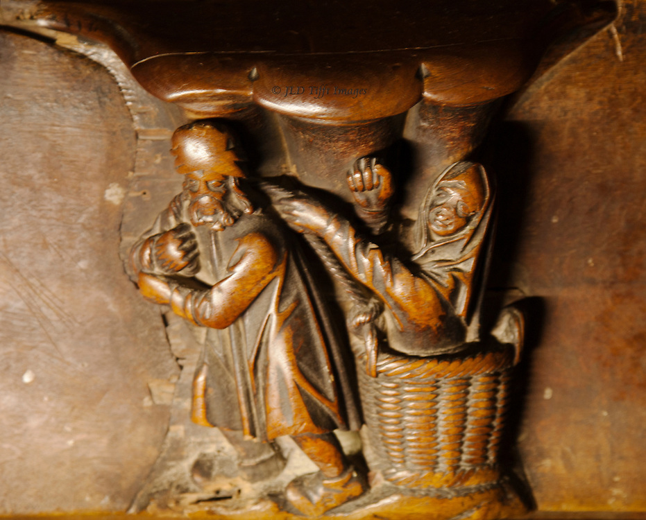 Toledo cathedral misericord: man pulling a basket along the ground, a woman in the basket gesturing and holding on to the rope he uses to pull her.  Both figures are rubbed and worn,