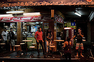 Residents are seen at a bar at the beginning of an incursion by security forces into 'Rocinha', one of Brazil's biggest slums controlled by drug traffickers, early on November 13, 2011, Rio de Janeiro, Brazil. Photo by Mauricio Lima for The New York Times